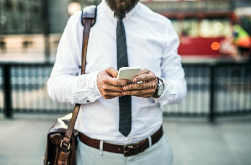 Unrecognizable businessman with smartphone standing on the street in city. Unrecognizable businessman with smartphone standing on the street in city, text royalty free stock photography