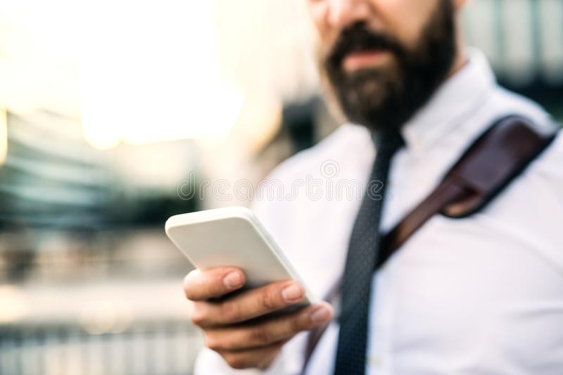 Unrecognizable businessman with smartphone standing on the street in city. Unrecognizable businessman with smartphone standing on the street in city, text stock images