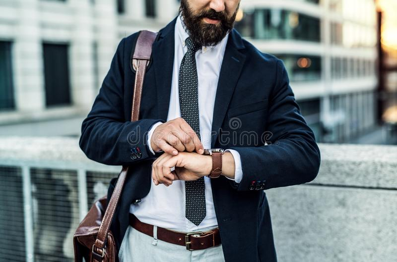 Unrecognizable businessman standing on the street in city, checking the time. Unrecognizable businessman with laptop suitcase standing on the street in city stock photos