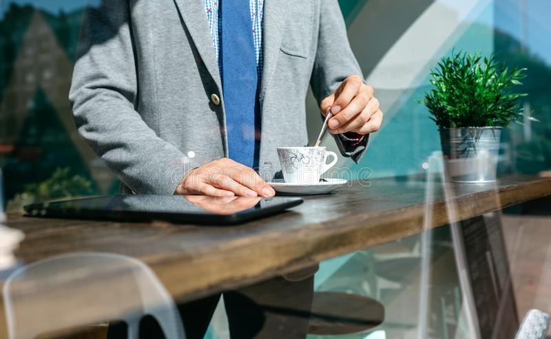 Unrecognizable businessman stirring coffee. In a coffee shop stock photography
