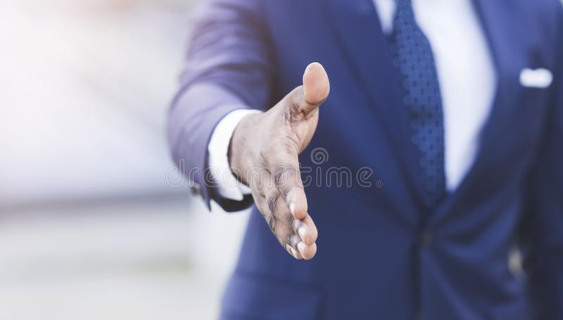 Unrecognizable Businessman Stretching Hand For Handshake Outdoor. Business Networking. Unrecognizable Afro Businessman Stretching Hand For Handshake Outdoor In stock image