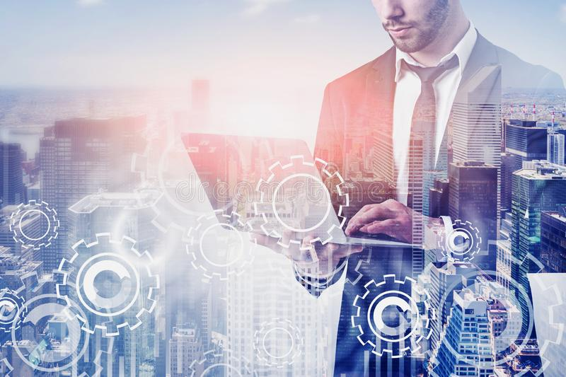 Man with laptop in city, gears. Unrecognizable businessman using laptop in city with double exposure of gears and graphs. Concept of smart city. Toned image stock photos