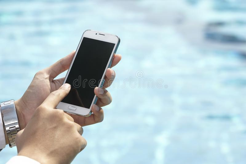 Unrecognizable businessman using phone. On pool side royalty free stock image