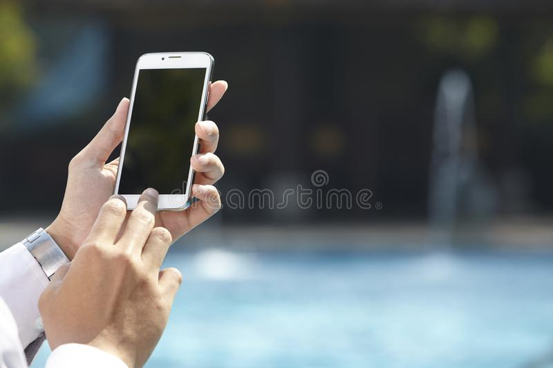 Unrecognizable businessman using phone. On pool side royalty free stock images