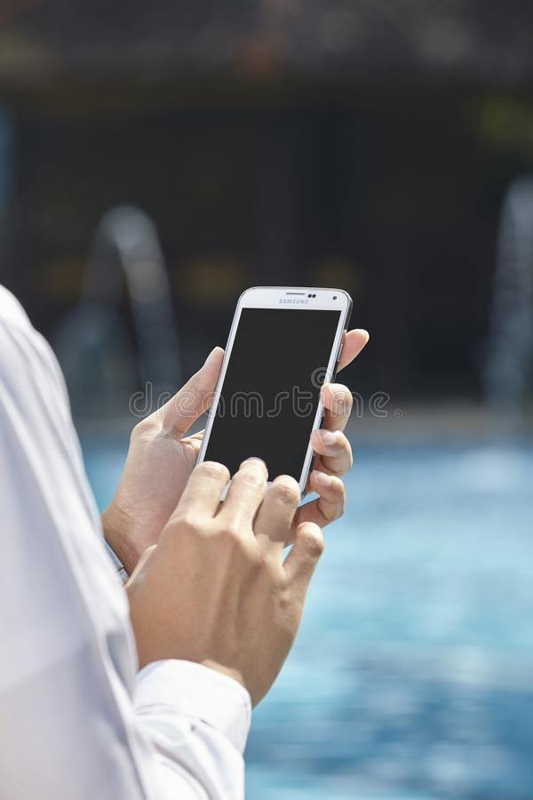 Unrecognizable businessman using phone. On pool side stock photo