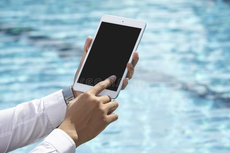 Unrecognizable businessman using phone. On pool side stock image