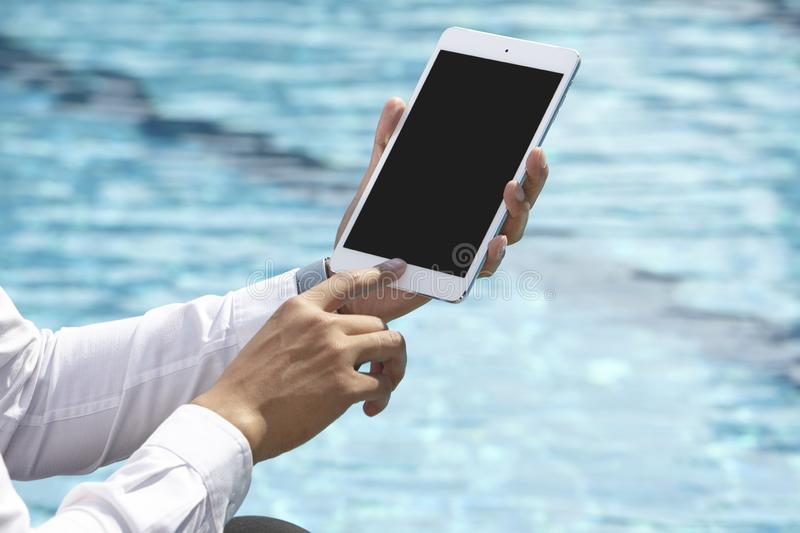 Unrecognizable businessman using phone. On pool side royalty free stock photos