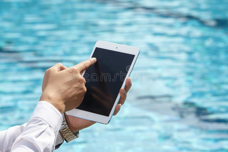 Unrecognizable businessman using phone. On pool side stock images
