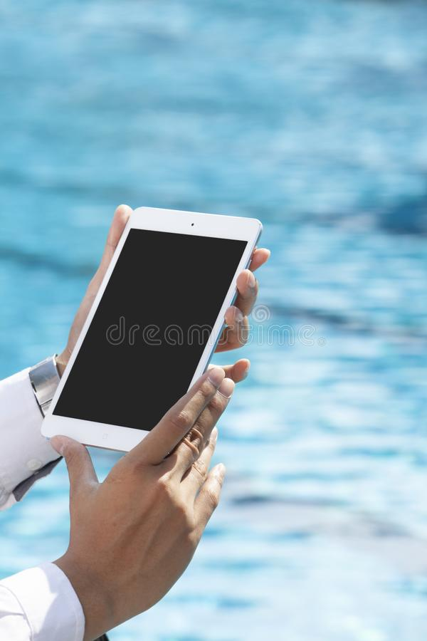 Unrecognizable businessman using tablet. On pool side stock photography