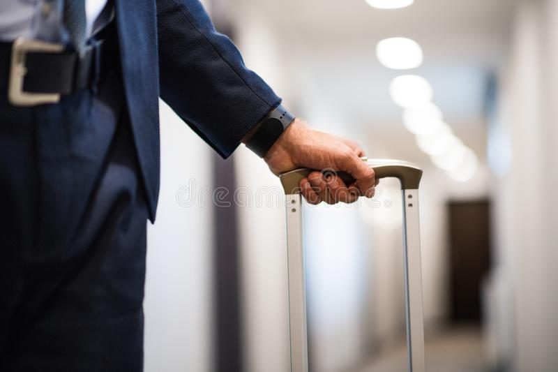 Unrecognizable businessman with luggage in a hotel corridor. Unrecognizable businessman walking with luggage in a hotel corridor.Close up royalty free stock photo