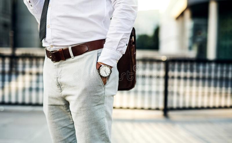 Unrecognizable businessman with watch standing on the street in city. Unrecognizable businessman with watch standing on the street in city, hand in pockets stock photo