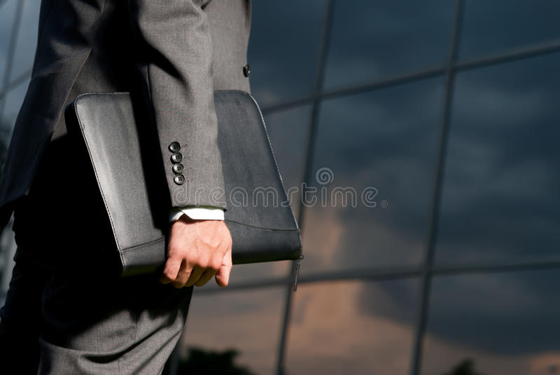 Unrecognizable businessman working late. Unrecognizable businessman with suitcase working late concept stock image
