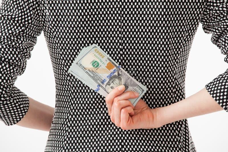 Unrecognizable businesswoman hiding money behind back stock image
