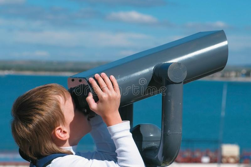 Unrecognizable chłopiec spojrzenia przez lornetek przy morzem zdjęcie royalty free