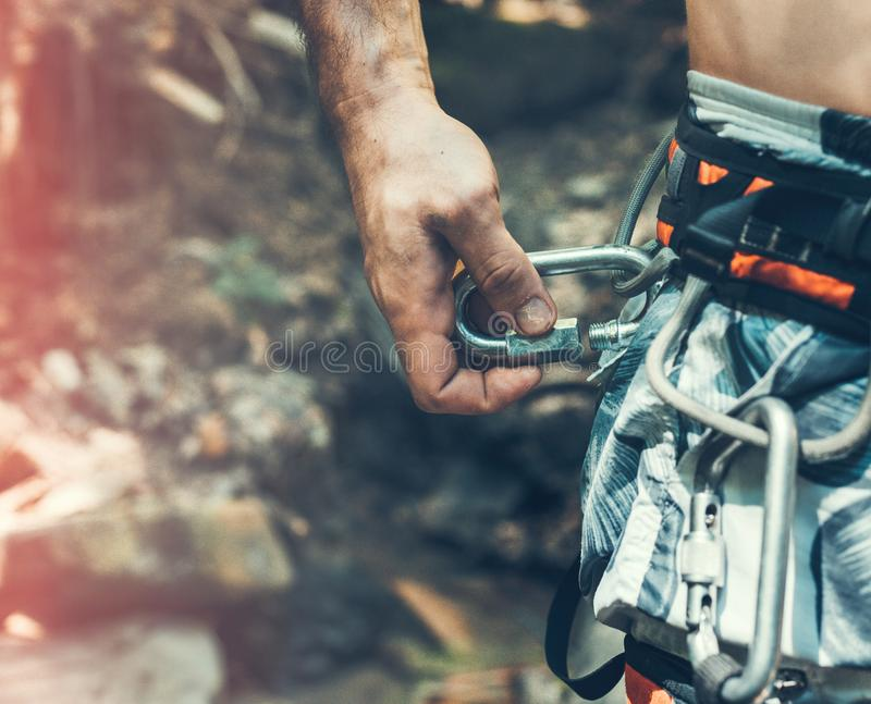 Unrecognizable Climber Man Wearing In Safety Harness Check Climbing Equipment Outdoor Activity. Unrecognizable man climbers check out climbing equipment outdoors stock image