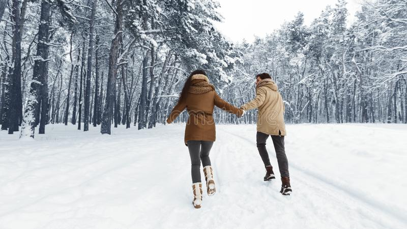 Unrecognizable Couple Running Through Winter Forest Holding Hands, Panorama royalty free stock images