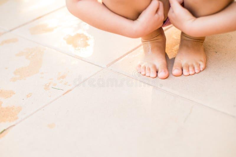 Unrecognizable dziecko w swimsuit przycupnięciu na bruku, mokra stopa fotografia stock