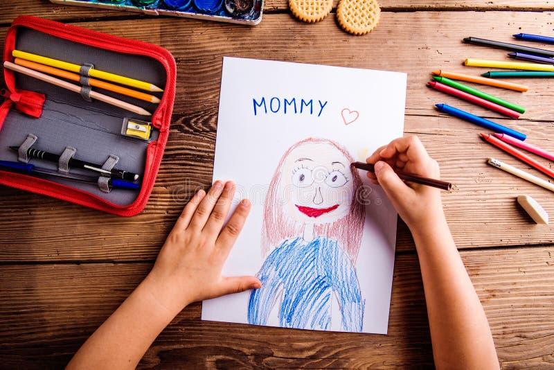 Unrecognizable dziewczyna rysunku obrazek jej matka Drewniany backgr obraz royalty free