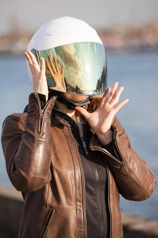 Unrecognizable European woman motorcyclist with white open face helmet with closed mirrored visor stock images