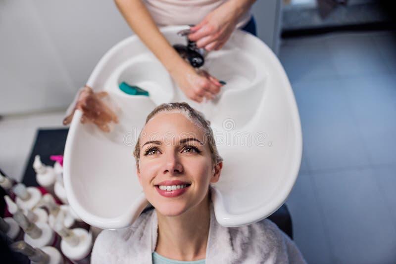 Unrecognizable fachowego fryzjera płuczkowy włosy jej kawaler fotografia stock
