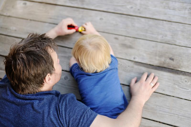 Unrecognizable father with his little son playing with toy cars royalty free stock photo