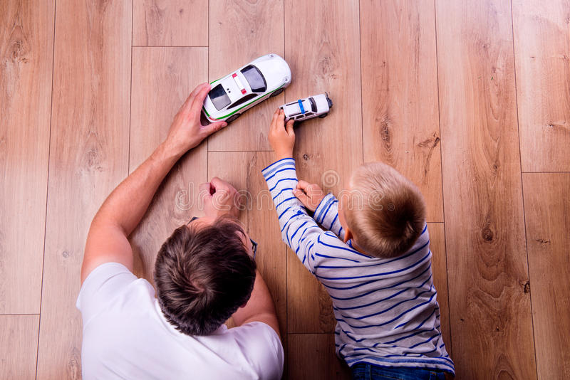 Unrecognizable father with his son playing with cars stock image