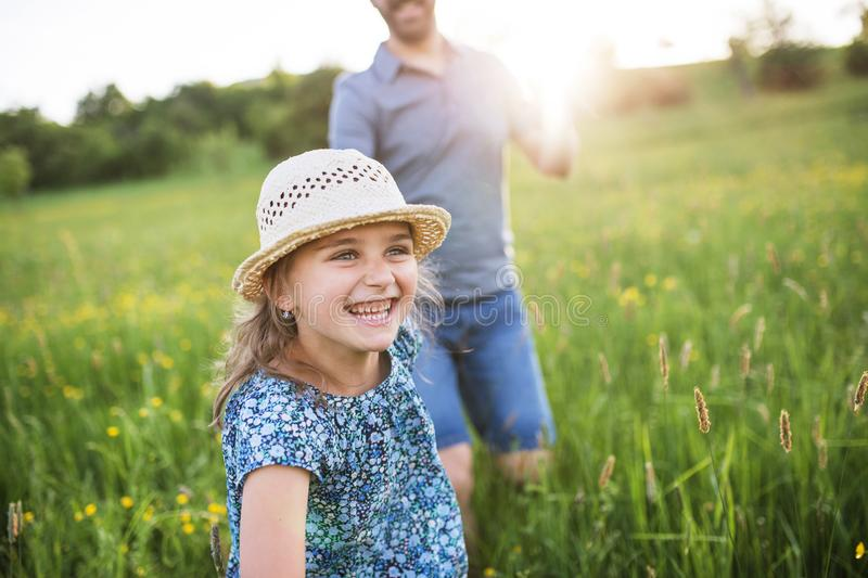 Father with a small daughter running in spring nature. royalty free stock photo