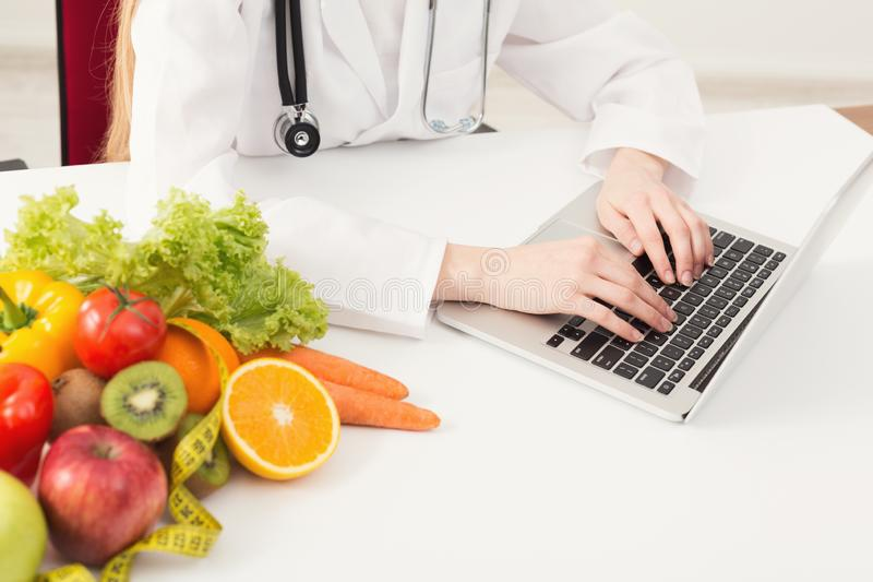 Unrecognizable female nutritionist working on laptop stock photos