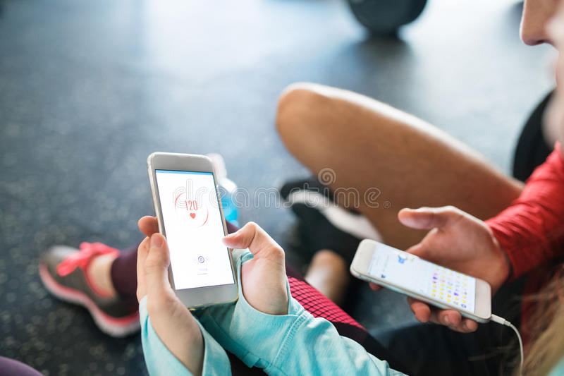 Unrecognizable fit couple in gym with smartphones. stock image