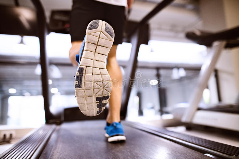 Unrecognizable fit hispanic man in gym running on treadmill. stock photo