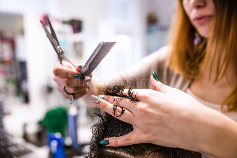 Unrecognizable fryzjera tnący włosy jej młody klient obraz stock