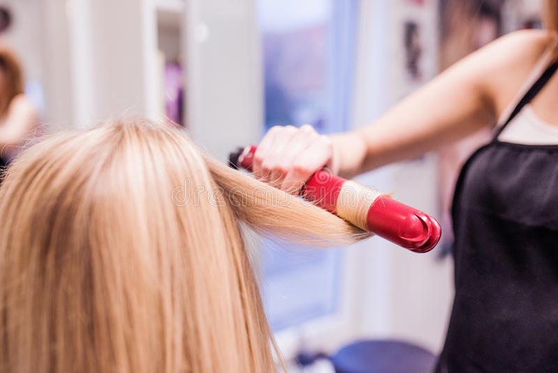 Unrecognizable hairdresser creating hairstyle for her beautiful stock images