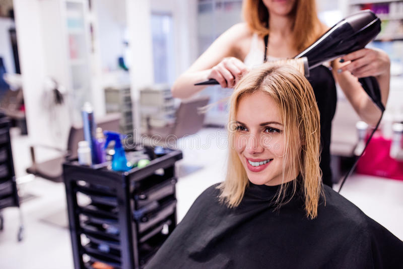 Unrecognizable hairdresser drying hair of her beautiful young cl royalty free stock images