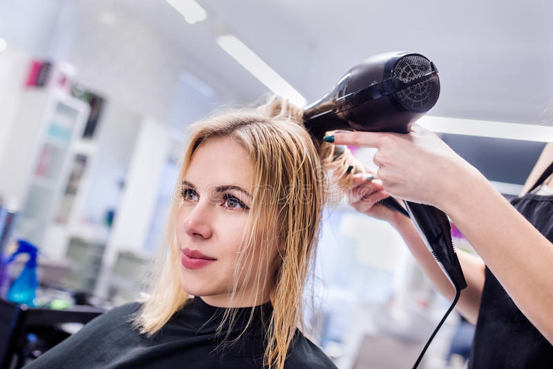 Unrecognizable hairdresser drying hair of her beautiful young cl royalty free stock photo