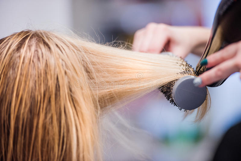 Unrecognizable hairdresser drying hair of her beautiful young cl royalty free stock photography