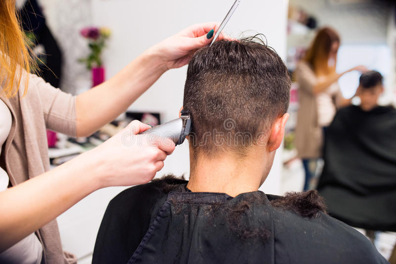 Unrecognizable hairdresser shaving head of her young client. stock photo