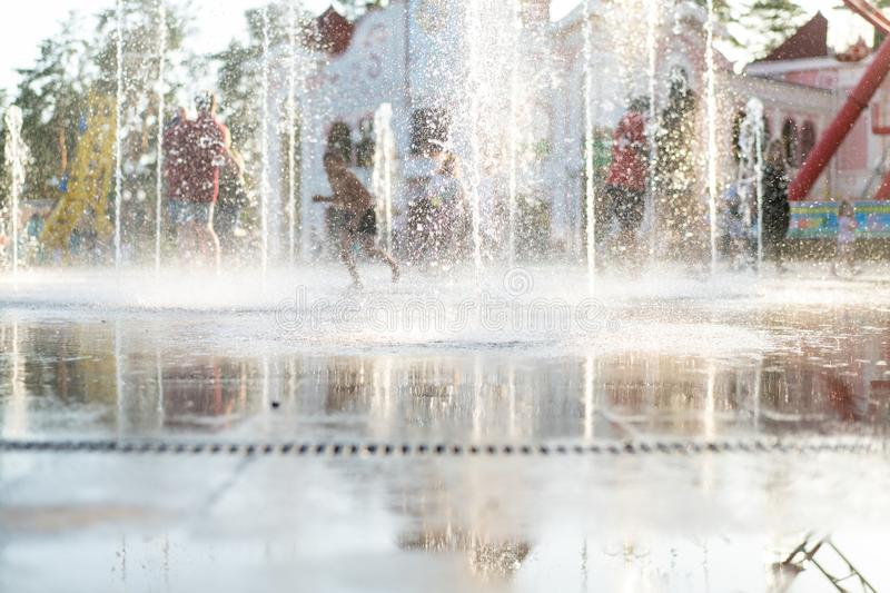 Unrecognizable Happy kids have fun playing in city dry water fountain on hot summer day royalty free stock image