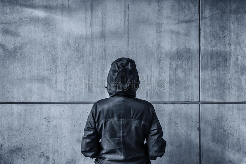 Unrecognizable hooded female person facing concrete wall as insu. Rmountable obstacle, young adult woman in urban surrounding confronting problems and royalty free stock image
