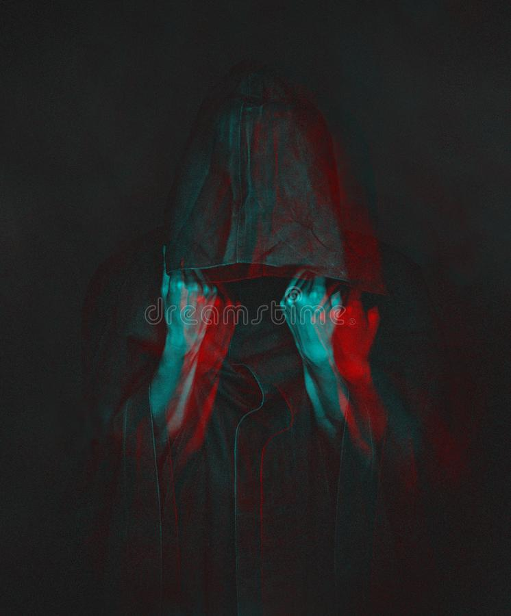 Anaglyph effect of human in black coat with a hood. stock image