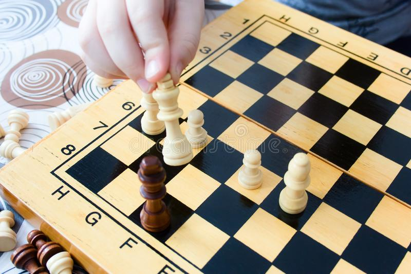 Kid playing chess at home, closeup of a child`s hand moves a chess piece. Unrecognizable kid playing chess at home, closeup of a child`s hand moves a chess piece royalty free stock image