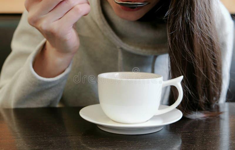 Unrecognizable kobieta pije gorącej herbaty od filiżanki z łyżką Zamyka w górę ręk fotografia royalty free