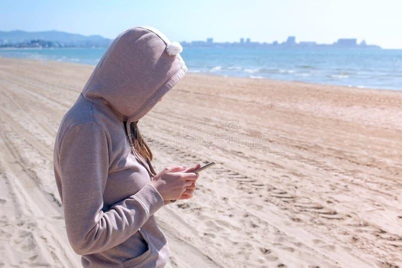 Unrecognizable kobieta pisać na maszynie na telefonie na plaży morzem zdjęcie stock