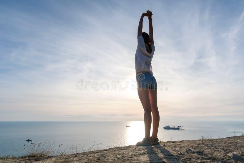 Unrecognizable kobieta w lekkiej bluzce i drelichowi skróty rozciąga na wzgórzu z seascape Popieramy widok zdjęcie royalty free