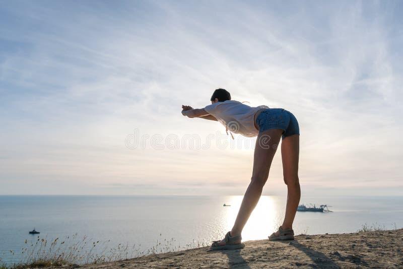 Unrecognizable kobieta w lekkiej bluzce i drelichu zwiera rozciąganie na wzgórzu z seascape Bocznym widokiem zdjęcia stock