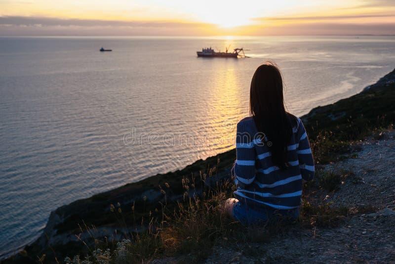 Unrecognizable kobieta w pasiastym pulowerze podziwia zmierzch na górze z seascape widoku plecy widokiem zdjęcie royalty free