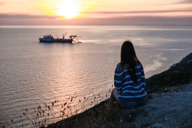Unrecognizable kobieta w pasiastym pulowerze podziwia zmierzch na górze z seascape widoku plecy widokiem zdjęcia royalty free