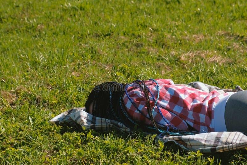 Unrecognizable kobieta z błękitnym afrykaninem splata dosypianie na gazonie w parku fotografia royalty free