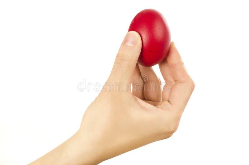 Unrecognizable kobiety ręka trzyma up dla jajka puka czerwonego Wielkanocnego jajko zdjęcie stock
