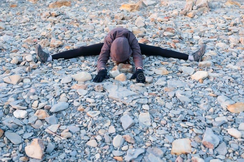 Unrecognizable kobiety rozciąganie na otoczaka brzeg w wiośnie Ubierający w kurtce i leggins zdjęcie royalty free