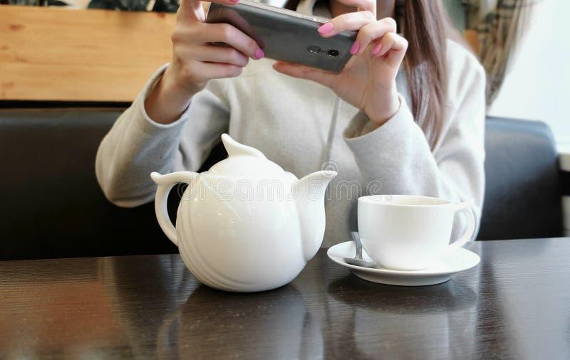 Unrecognizable kobiety ` s wręcza obrazki teapot i filiżanka w kawiarni na jej telefonie komórkowym Frontowy widok obraz royalty free